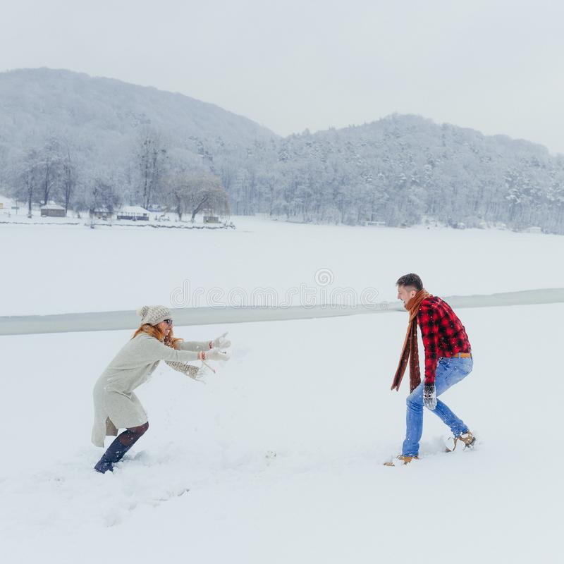 Pares loving que têm o prado nevado de jogo Forest Winter Christmas New Year das bolas da neve do divertimento imagens de stock royalty free