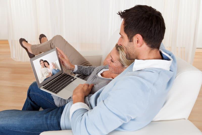 Pares Loving que têm a videoconferência foto de stock royalty free