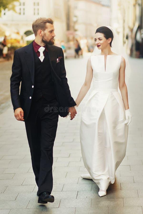 Pares luxuosos do casamento que guardam as mãos e que andam na rua da cidade fotos de stock