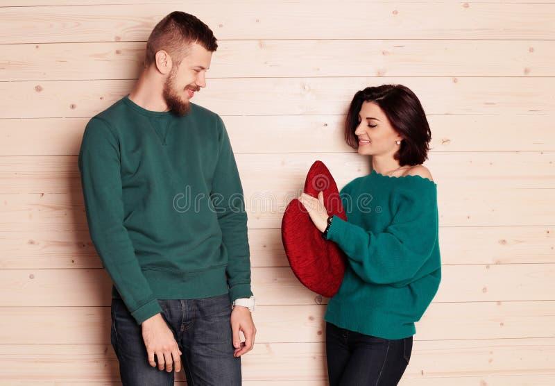 Pares macios na roupa ocasional, tendo o divertimento no estúdio, menina que guarda o coração vermelho grande fotografia de stock royalty free