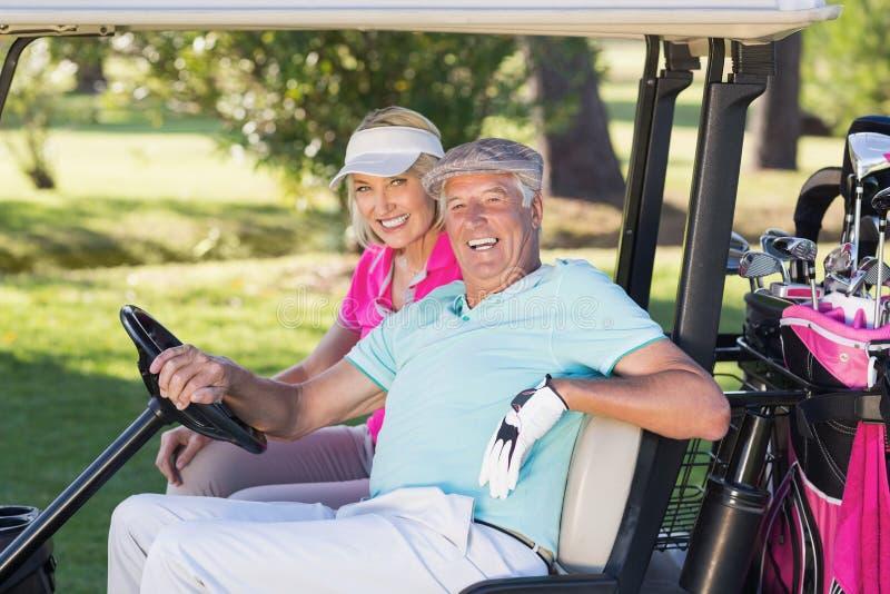 Pares maduros alegres do jogador de golfe que sentam-se no carrinho do golfe foto de stock