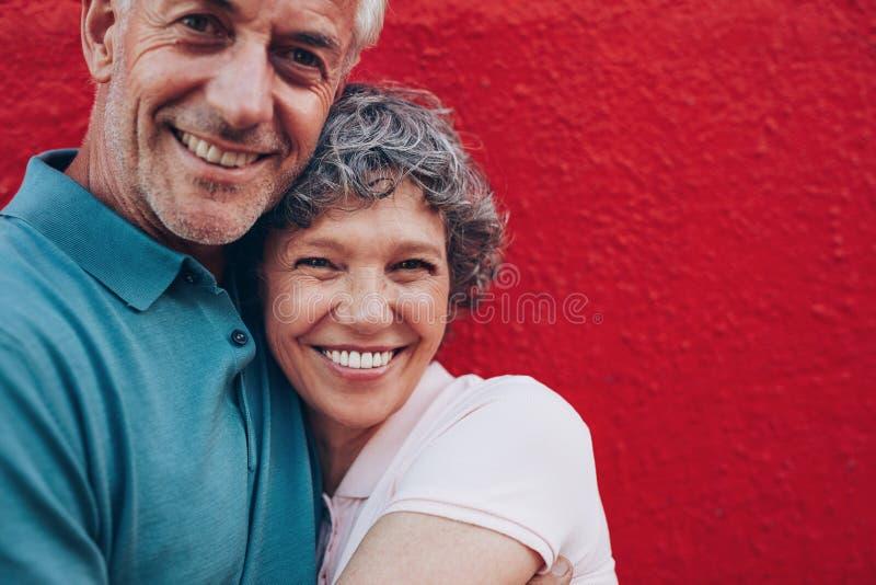 Pares maduros alegres que abraçam-se foto de stock