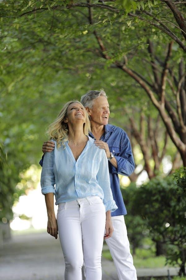 Pares maduros atrativos que levantam em um fundo verde da árvore foto de stock royalty free