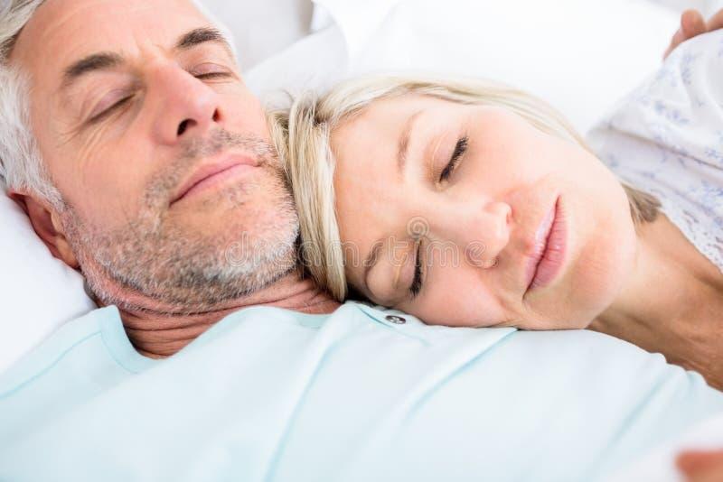 Pares maduros cariñosos que duermen en cama imagenes de archivo