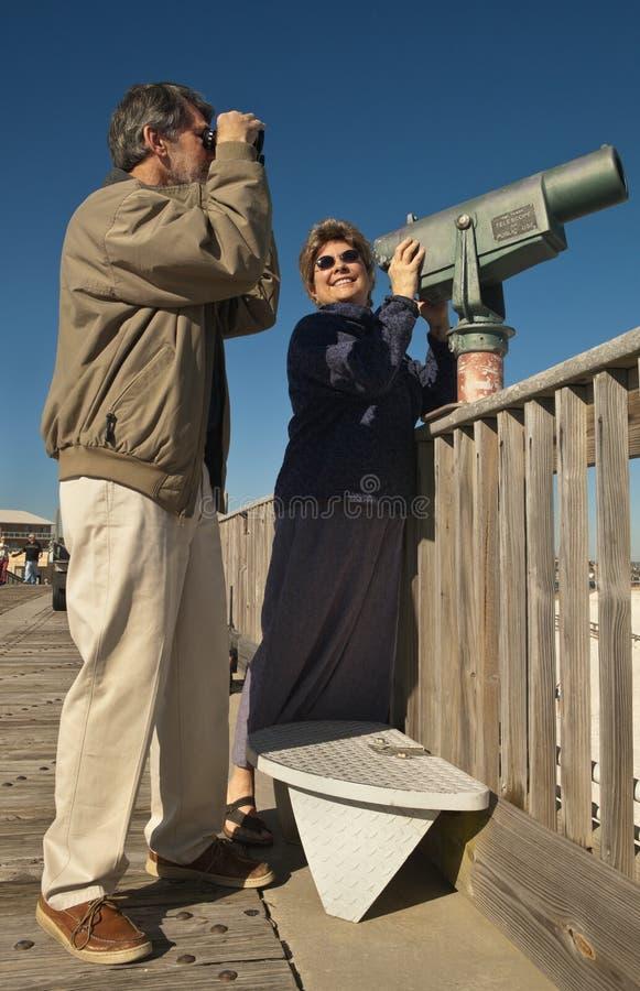 Pares maduros com telescópio e binóculos fotos de stock royalty free