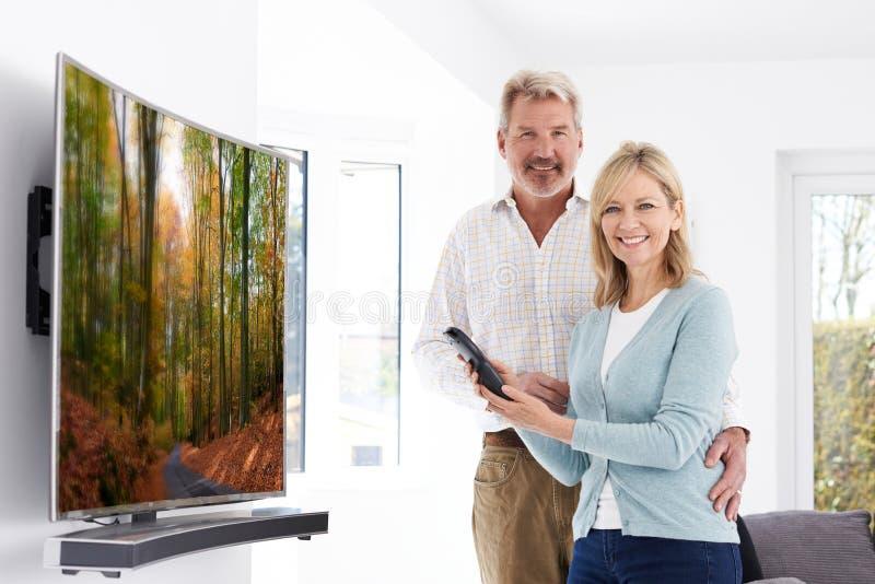 Pares maduros com a televisão curvada nova da tela em casa imagem de stock royalty free