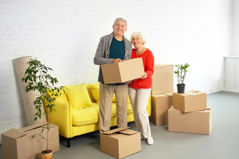 Pares maduros con las cajas después de trasladarse a nueva casa imágenes de archivo libres de regalías