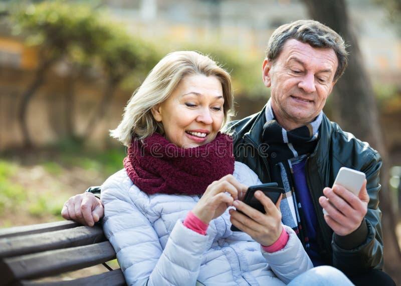 Pares maduros con smartphones al aire libre fotos de archivo