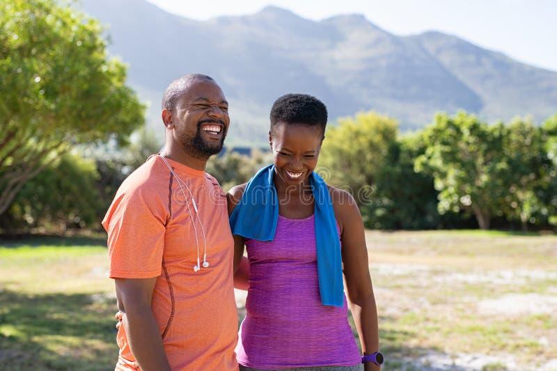Pares maduros da aptidão africana que riem do parque imagem de stock royalty free