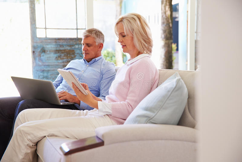 Pares maduros em casa na sala de estar usando dispositivos de Digitas imagens de stock