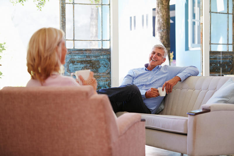 Pares maduros em casa que relaxam na sala de estar com bebida quente imagens de stock royalty free