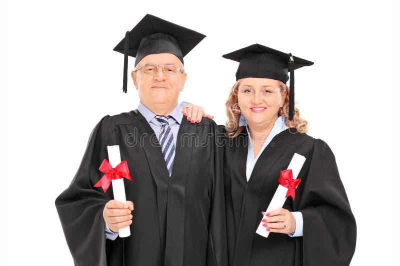 Pares maduros en vestidos de la graduación con los diplomas imagen de archivo