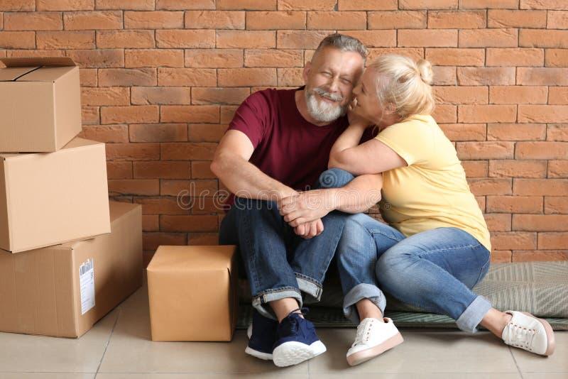 Pares maduros felices con las cajas móviles que se sientan en la alfombra en el nuevo hogar foto de archivo