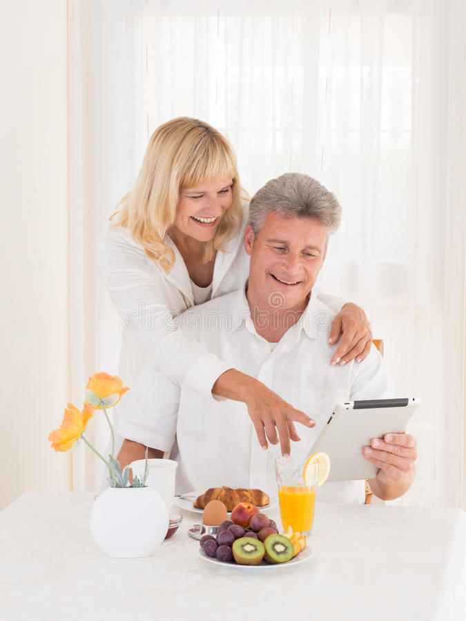 Pares maduros felices en el desayuno que señala en la tableta fotografía de archivo