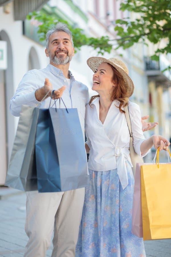 Pares maduros felices juguetones que vuelven de hacer compras en el centro de la ciudad fotos de archivo libres de regalías