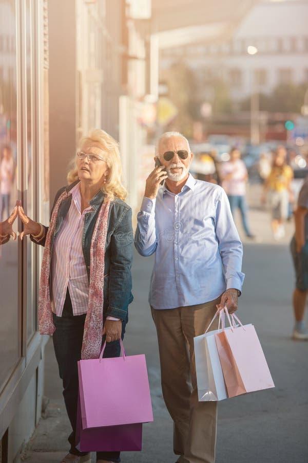 Pares maduros felices que caminan con sus compras de las compras en un día soleado imagen de archivo