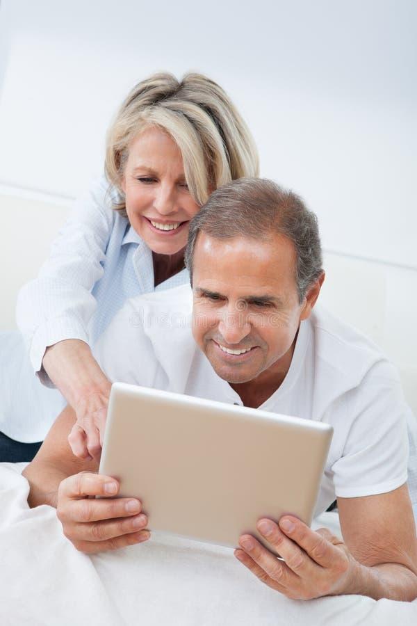 Pares maduros felices que miran la tableta digital fotografía de archivo