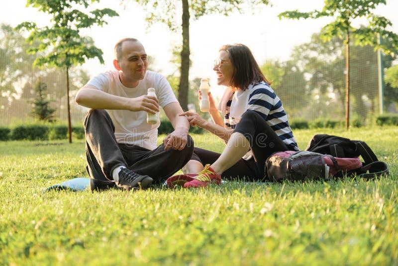 Pares maduros felices que se sientan en el parque en la estera de la aptitud, yogur de consumición de reclinación después de ejer imagenes de archivo