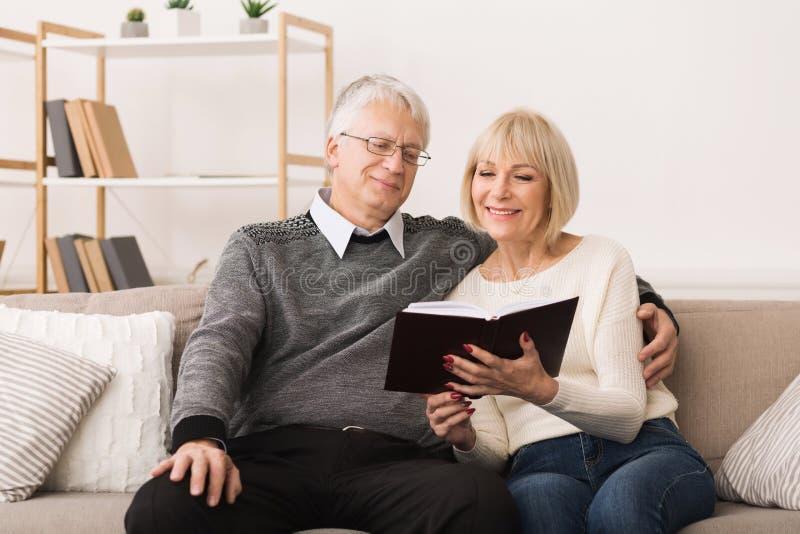 Pares maduros felices que tienen resto en el sofá en casa foto de archivo libre de regalías