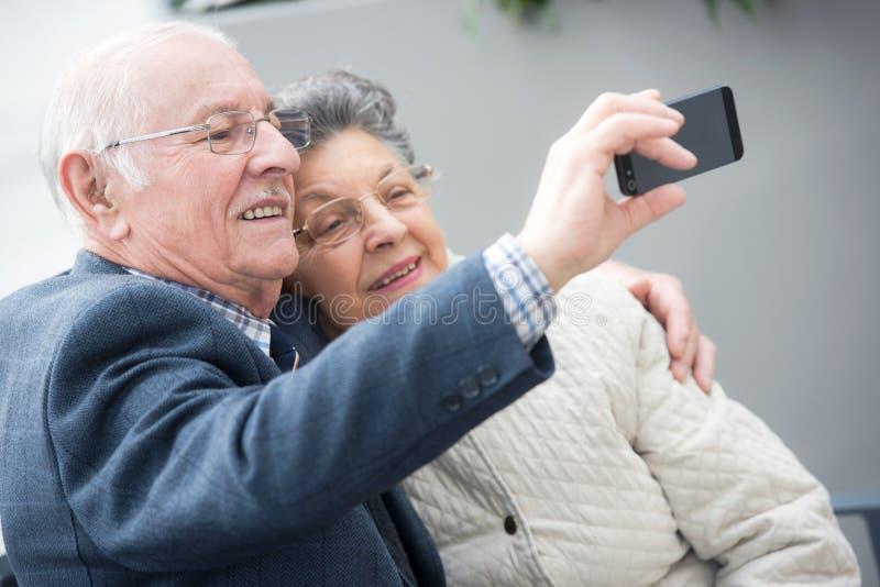Pares maduros felices que toman el selfie con el teléfono imagen de archivo