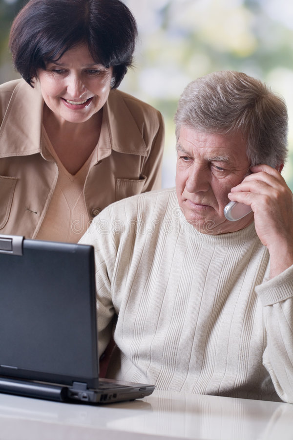 Pares maduros felices que trabajan en la computadora portátil fotos de archivo libres de regalías