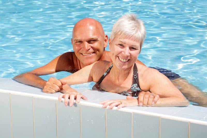 Pares maduros felizes na piscina fotografia de stock royalty free