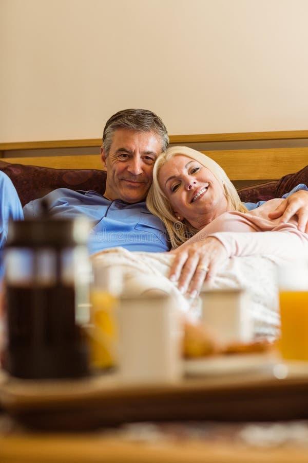 Pares maduros felizes que comem o café da manhã na cama foto de stock