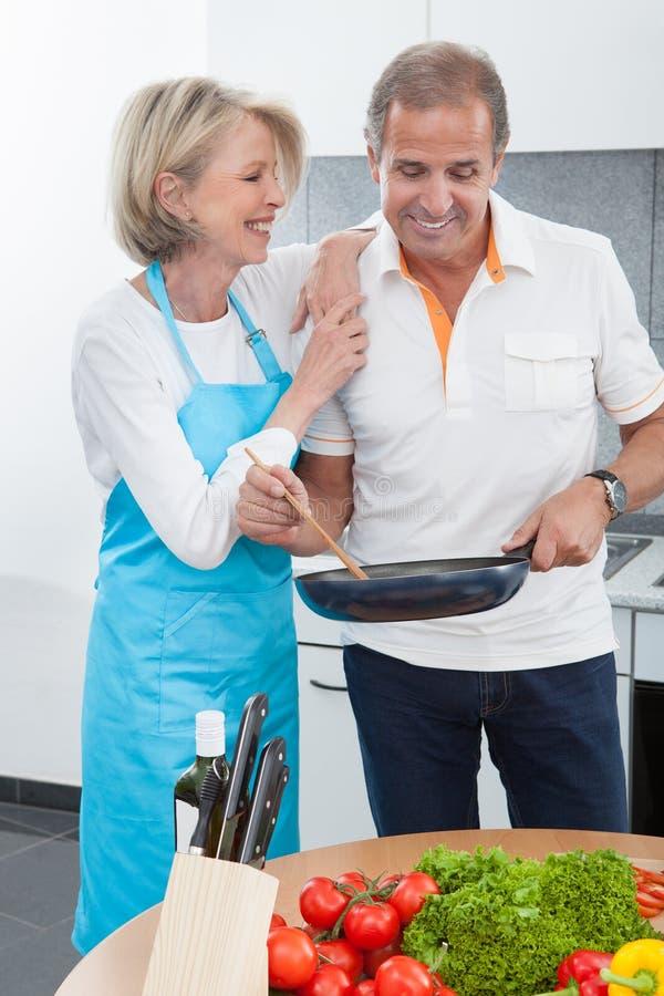 Pares maduros felizes que cozinham o alimento na cozinha fotografia de stock royalty free