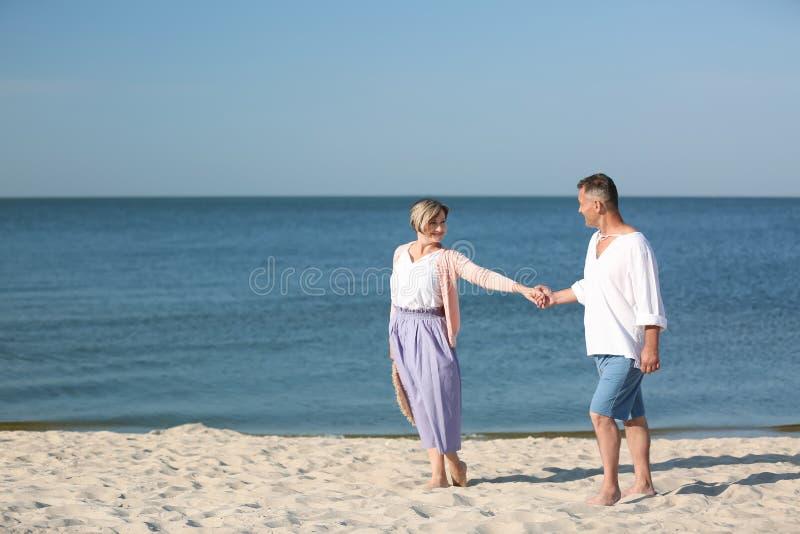 Pares maduros felizes que guardam as mãos na praia foto de stock royalty free