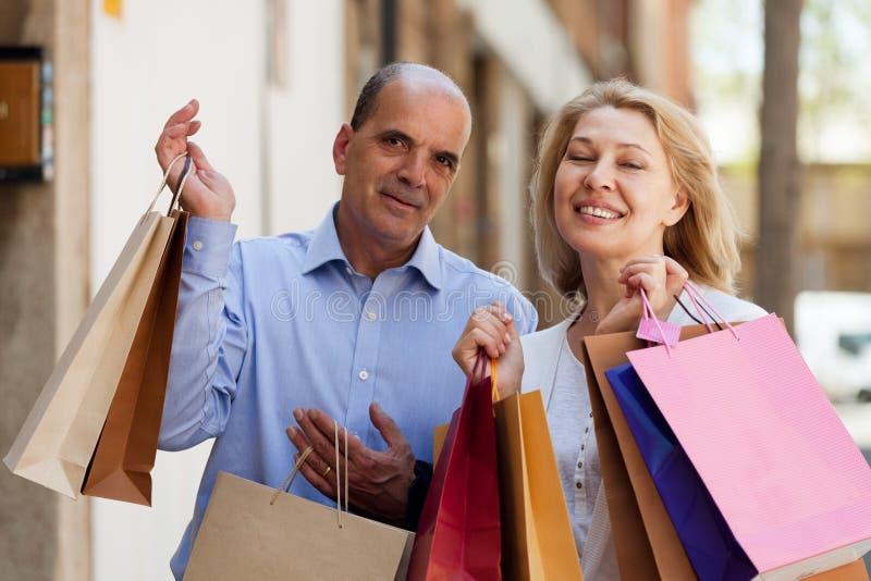Pares maduros felizes que guardam sacos após a compra fotografia de stock