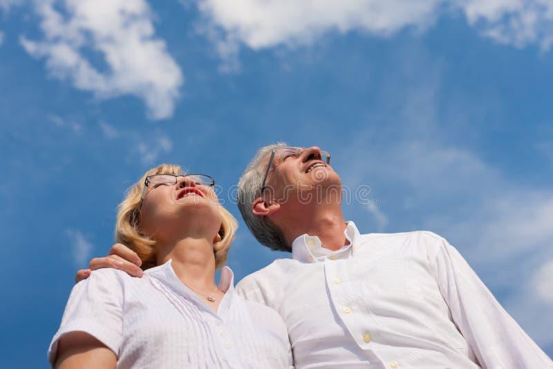Pares maduros felizes que olham ao céu azul imagem de stock