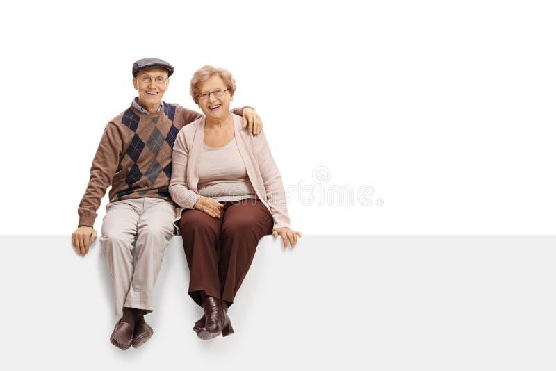 Pares maduros felizes que sentam-se em um painel imagens de stock royalty free