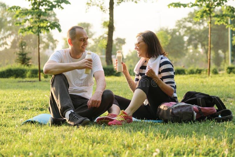 Pares maduros felizes que sentam-se no parque na esteira da aptidão, iogurte bebendo de descanso após exercícios dos esportes fotografia de stock