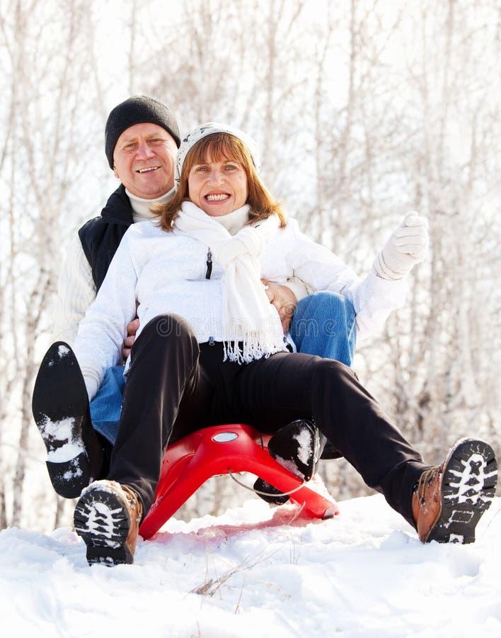 Pares maduros felizes que sledding fotografia de stock royalty free