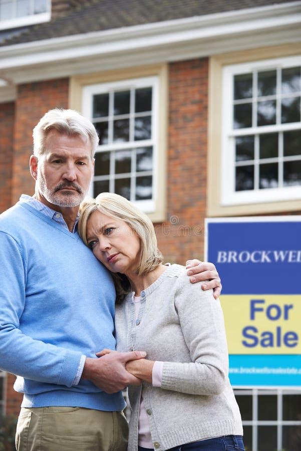 Pares maduros forçados para vender em casa com os problemas financeiros fotos de stock royalty free