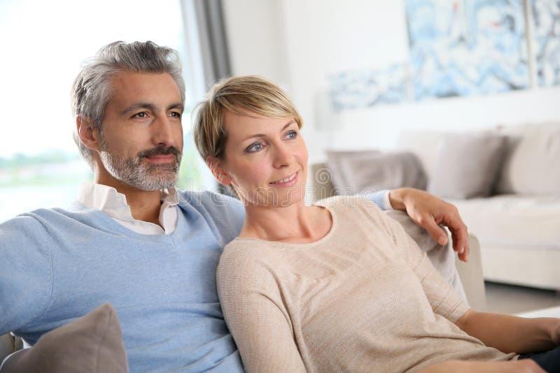 Pares maduros loving que relaxam no sofá imagens de stock royalty free