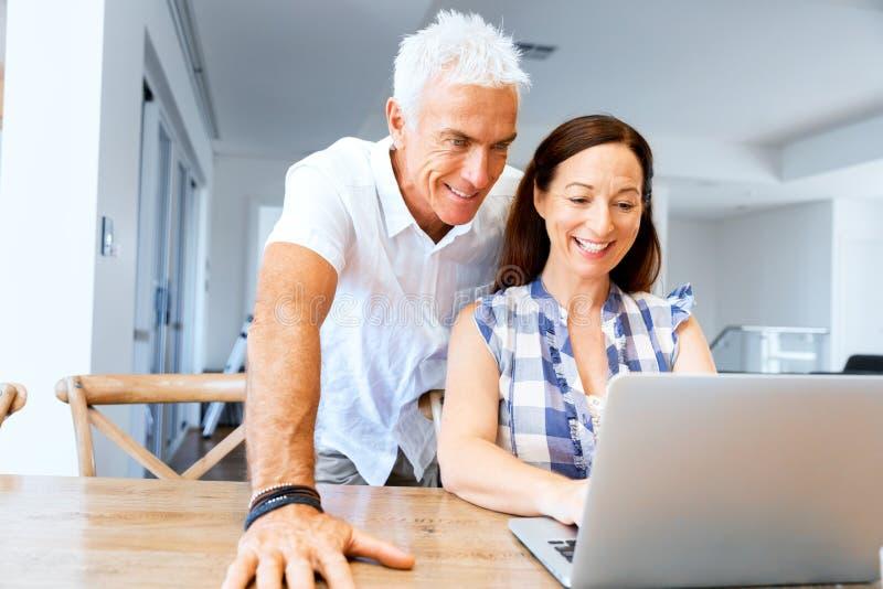 Pares maduros modernos felices que trabajan en el ordenador portátil en casa imágenes de archivo libres de regalías