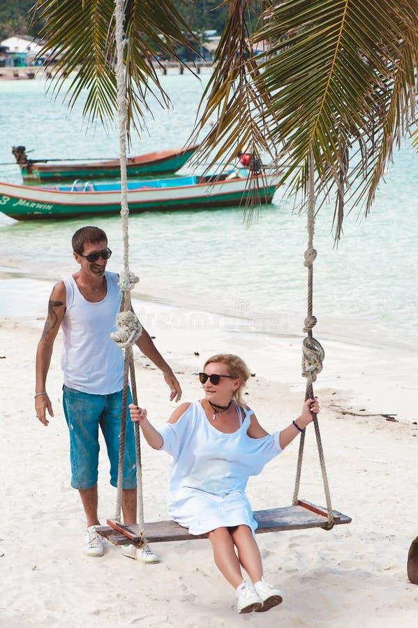 Pares maduros nas férias na praia, uma mulher no balanço imagens de stock royalty free