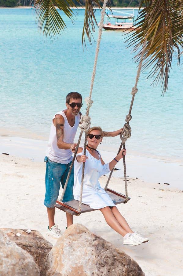 Pares maduros nas férias na praia, uma mulher no balanço foto de stock