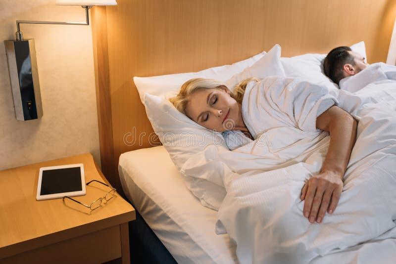 pares maduros nos roupões que dormem na cama e na tabuleta digital com os monóculos na tabela no hotel fotografia de stock