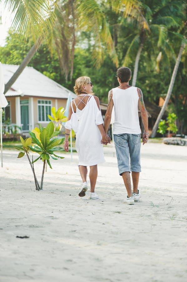 Pares maduros que abraçam o passeio na praia fotos de stock