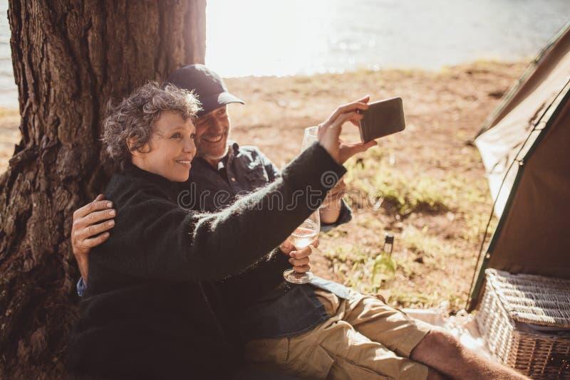 Pares maduros que acampan cerca de un lago que toma el selfie imagenes de archivo