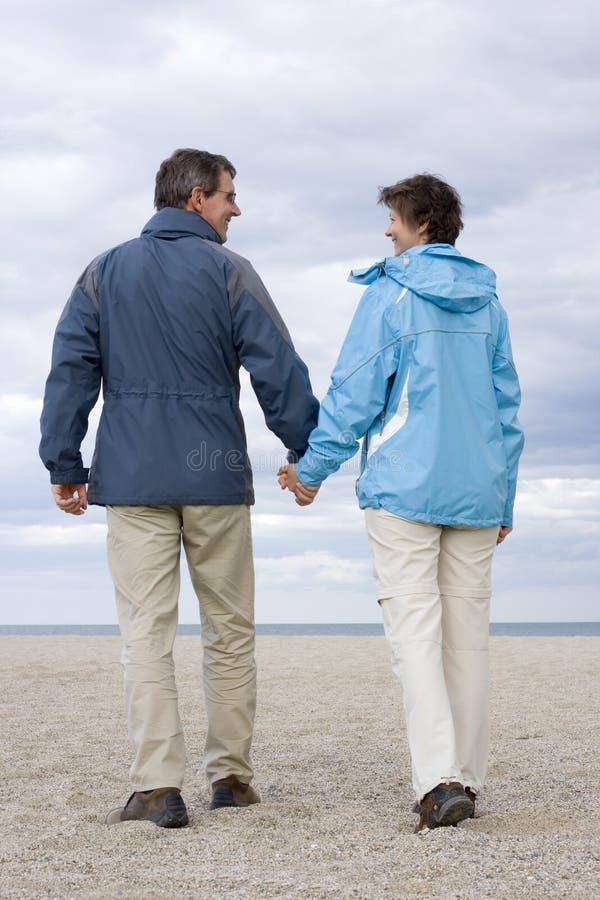 Pares maduros que andam em uma praia imagens de stock