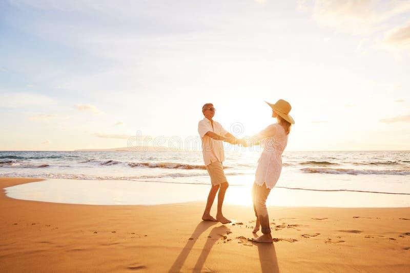 Pares maduros que andam na praia no por do sol fotografia de stock royalty free
