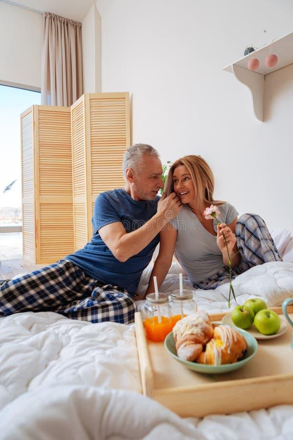 Pares maduros que apreciam a manhã romântica que come o café da manhã na cama foto de stock