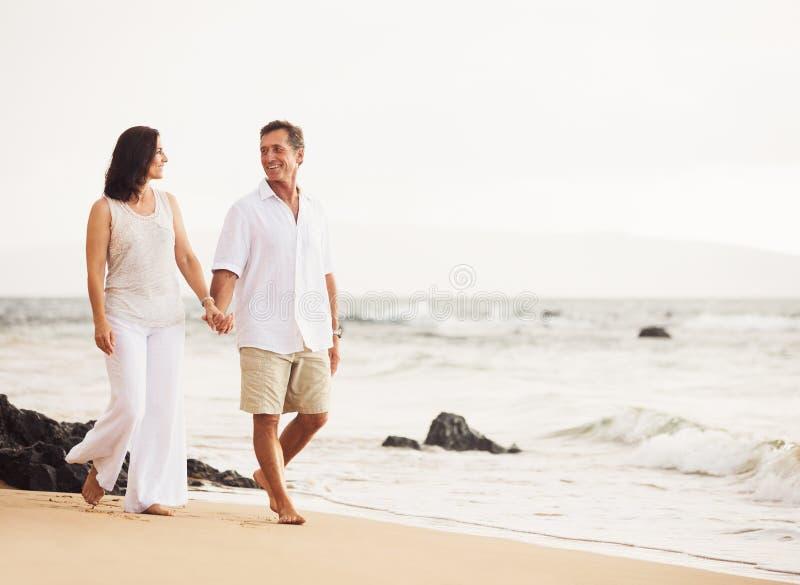 Pares maduros que apreciam o por do sol na praia fotografia de stock
