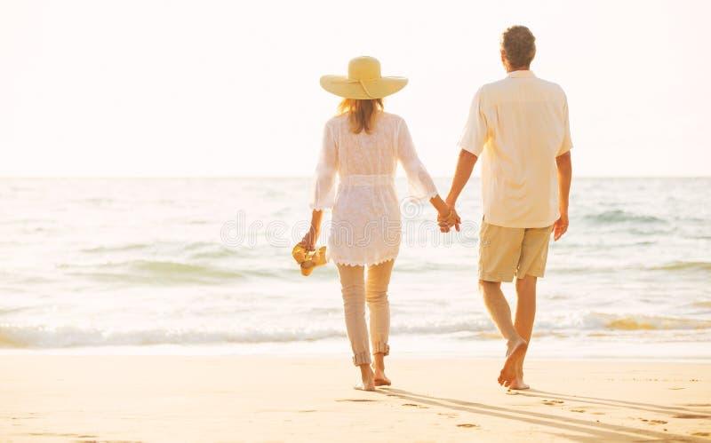 Pares maduros que caminan en la playa en la puesta del sol fotografía de archivo libre de regalías