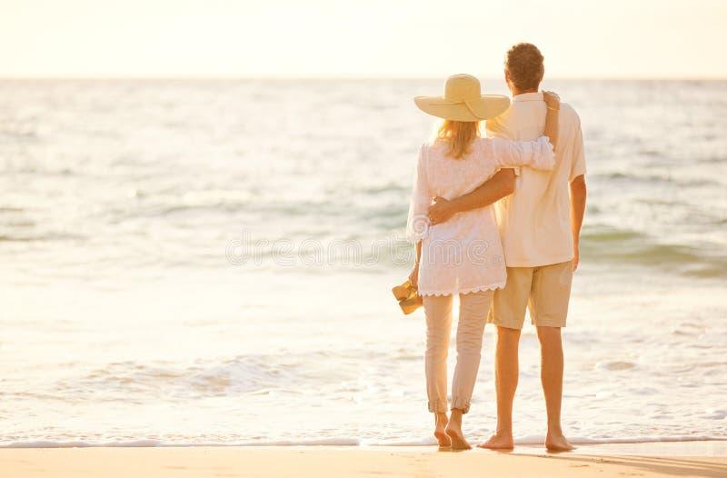 Pares maduros que caminan en la playa en la puesta del sol fotografía de archivo