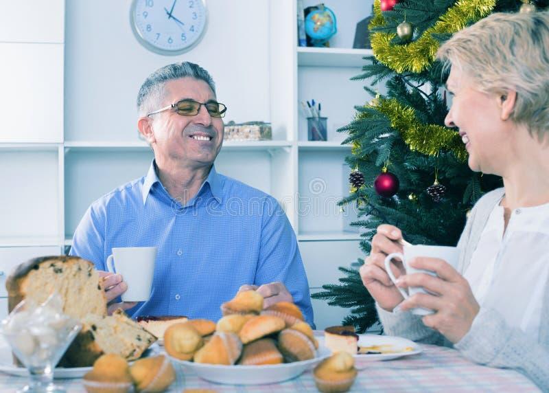 Pares maduros que comem o café da manhã na tabela festiva do Natal fotos de stock royalty free