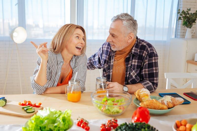 Pares maduros que comem a salada saudável do jardim e que bebem o suco fotos de stock